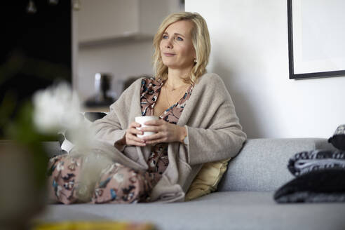 Blond woman relaxing at home sitting on couch - RBF07051