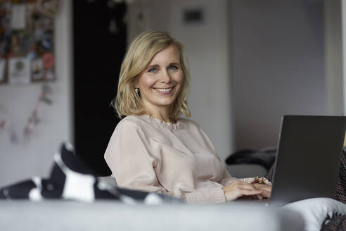Portrait of smiling blond woman using laptop at home - RBF07060