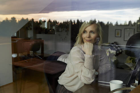 Portrait of blond woman with laptop behind windowpane at home - RBF07063