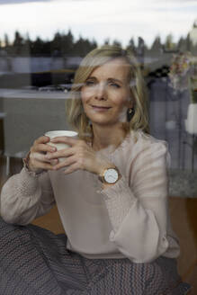 Smiling blond woman holding coffee cup behind windowpane at home - RBF07066