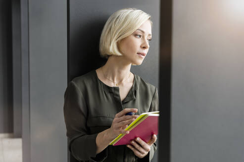 Portrait of pensive businesswoman with notebooks looking at distance - BMOF00173