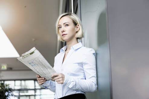 Portrait of blond businesswoman with newspaper - BMOF00182