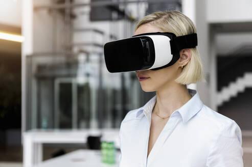 Woman wearing VR glasses in office - BMOF00185
