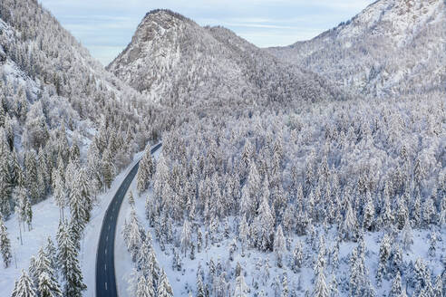 Germany, Bavaria, Aerial view of mountain highway and snow-covered forest in winter - MMAF01266