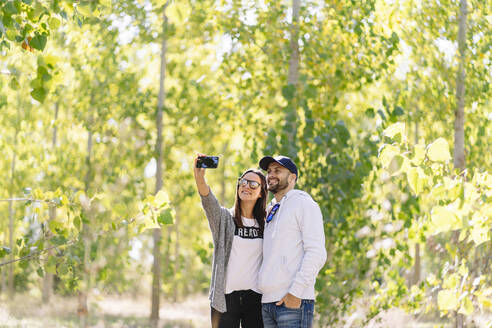 Smiling couple taking a selfie in a park - DGOF00429