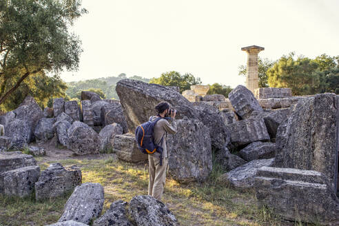 Greece,Olympia, Male tourist photographing ruins of ancient Temple of Zeus at sunset - MAMF01186