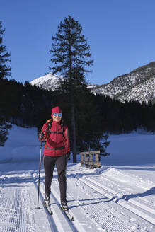Senior woman doing cross-country skiing with karwendal mountains in background, Bavaria, Germany - MRF02360