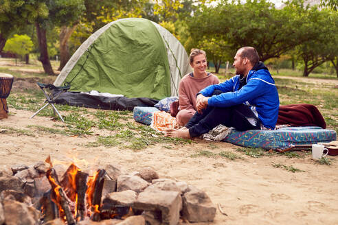 Young couple camping talking at campsite - CAIF23822