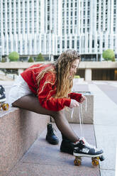 Young woman putting on roller skates in the city - KIJF02897