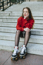 Young woman with roller skates sitting on stairs - KIJF02900