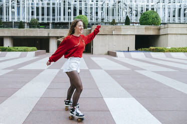 Happy young woman roller skating in the city - KIJF02903