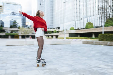 Happy young woman roller skating in the city - KIJF02906