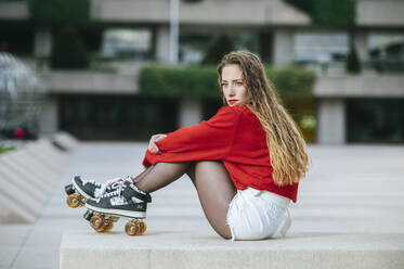 Young woman with roller skates sitting on a wall in the city - KIJF02912