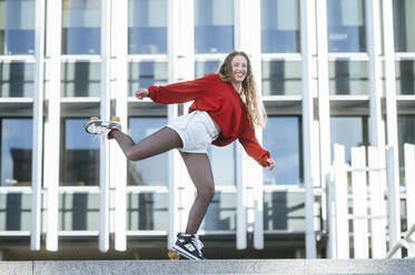 Portrait of happy young woman balancing on roller skates in the city - KIJF02915