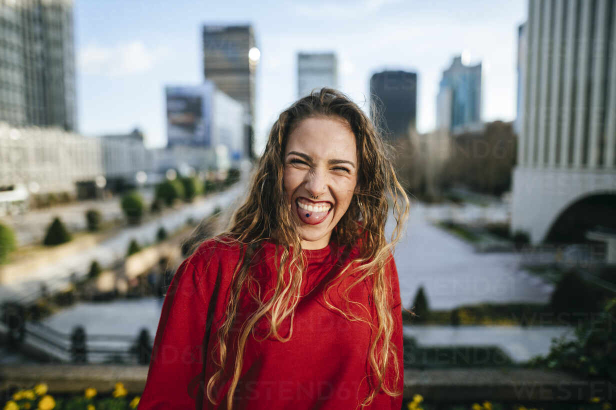Portrait of happy young woman in the city sticking out her tongue - KIJF02921 - Kiko Jimenez/Westend61