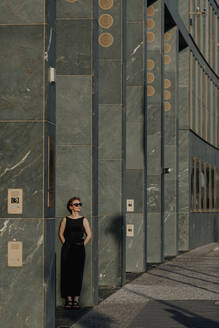 Red-haired woman with sunglasses, leaning on pillars in the city - OGF00137
