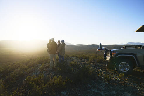 Safari tour group enjoying idyllic sunrise from hill South Africa - CAIF23944