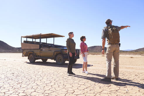 Safari tour guide talking tourists in sunny arid desert South Africa - CAIF23980