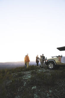 Safari tour group on hill at sunrise South Africa - CAIF24010