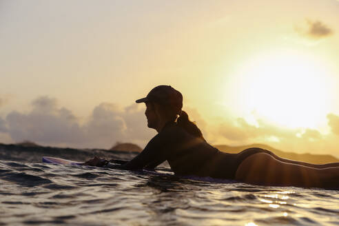Female surfer lying on surfboard in the evening - CAVF74872
