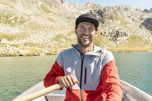 Young smiling man in a rowing boat, Lake Suretta, Graubuenden, Switzerland - HBIF00032