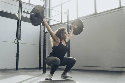 Young woman weightlifting in gym - MTBF00342