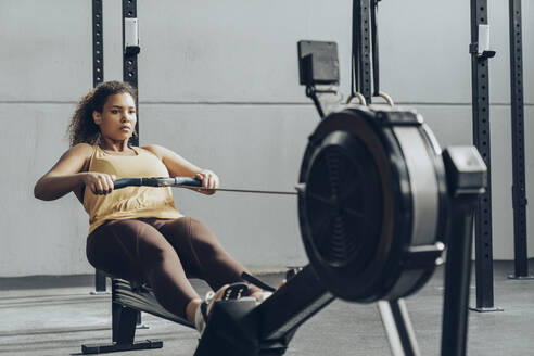 Young woman exercising in gym with rowing machine - MTBF00354