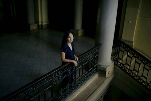 Portrait of serious woman leaning on banister in an old building looking at distance - OGF00148