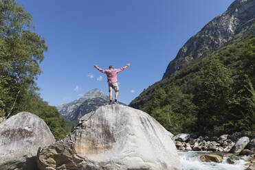 Man standing on rock at Verzasca river, Verzasca Valley, Ticino, Switzerland - GWF06459