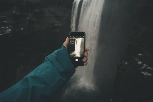 Young male taking a picture of waterfall with his smartphone - CAVF75060