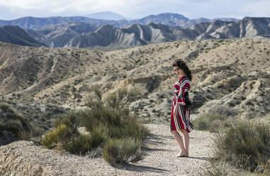Fashionable woman wearing striped dress in landscape, Almeria, Spain - LJF01307