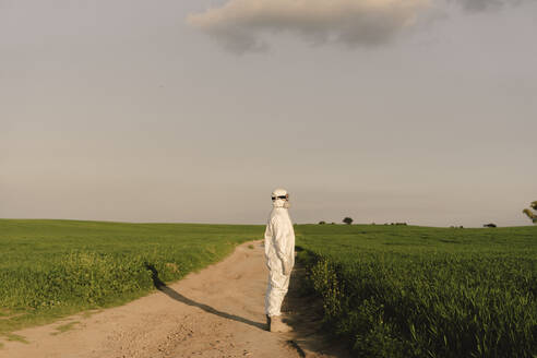 Man wearing protective suit and mask in the countryside - ERRF02630