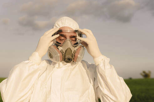 Portait of man with closed eyes wearing protective suit and mask - ERRF02636