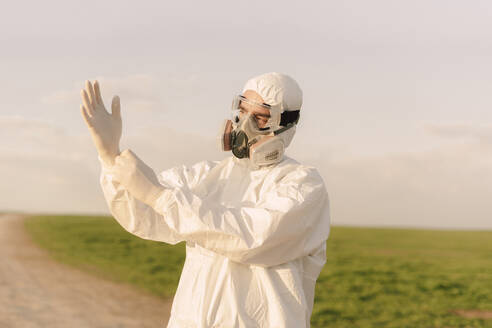 Man wearing protective suit and mask in the countryside putting on protective gloves - ERRF02642