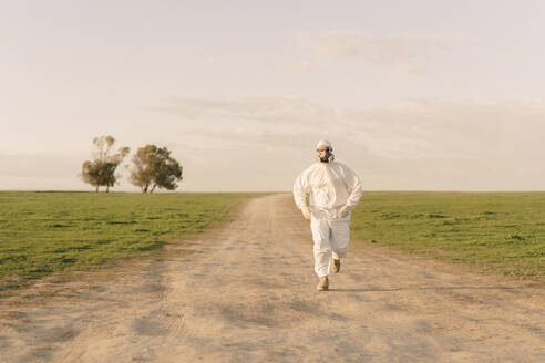 Man wearing protective suit and mask running on dirt track in the countryside - ERRF02645