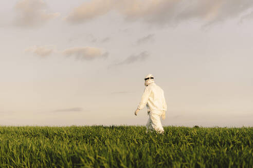 Rear view of man wearing protective suit walking in the countryside - ERRF02648