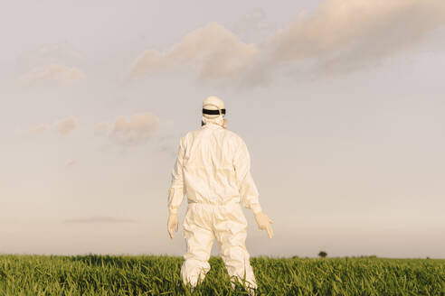 Rear view of man wearing protective suit in the countryside - ERRF02651
