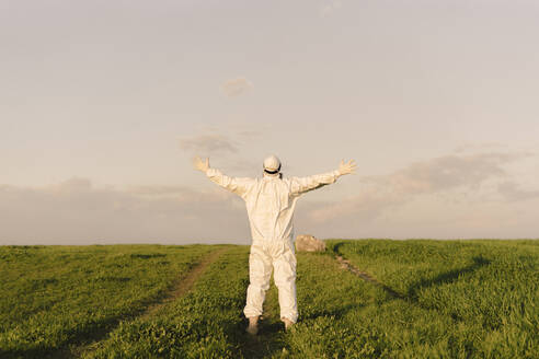 Rear view of man with outstetched arms wearing protective suit in the countryside - ERRF02657
