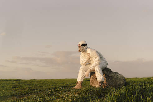 Man wearing protective suit and mask sitting on a rock in the countryside - ERRF02660