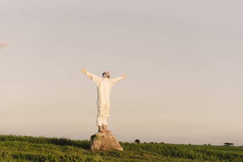 Man wearing protective suit and mask standing on a rock in the countryside - ERRF02666
