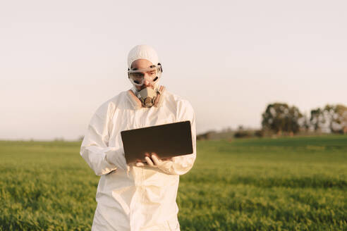 Man wearing protective suit and mask in the countryside using laptop - ERRF02675