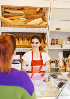 Young woman serving female customer in a bakery - LJF01325