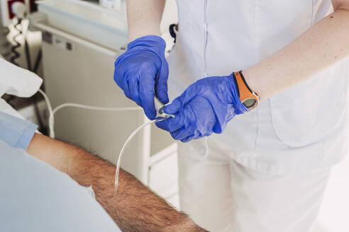 Nurse adjusting iv drip for patient lying in hospital bed - LJF01355