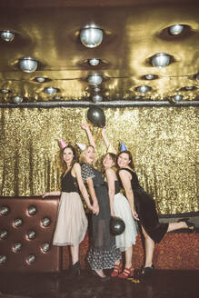 Portrait of four happy women wearing party hats in a club - HBIF00051