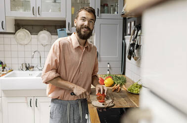 Young man standing in kitchen, chopping tomatoes, smiling - PESF01808