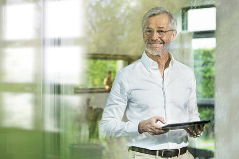 Smiling senior man with grey hair in modern design living room holding tablet - SBOF02096