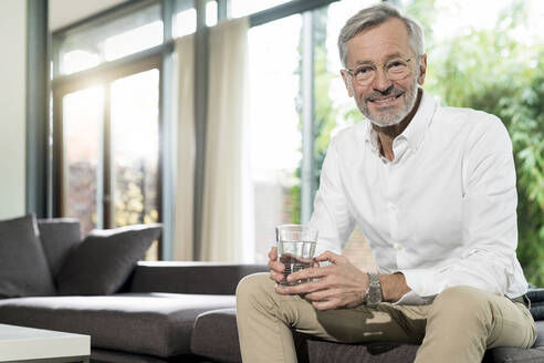 Portrait of smiling senior man in modern design living room sitting on couch holding glass of water - SBOF02108