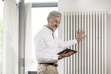 Senior man with grey hair in modern design living room holding tablet checking his smarthome heating - SBOF02111
