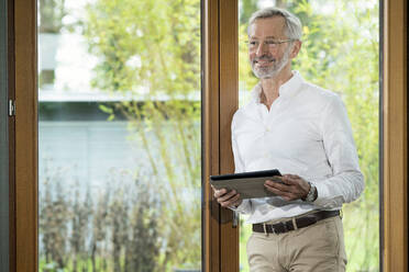 Smiling senior man with grey hair in modern design living room standing at window holding tablet - SBOF02114