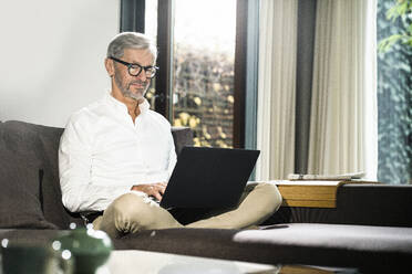 Senior man with grey hair in modern design living room working on laptop in home office - SBOF02123